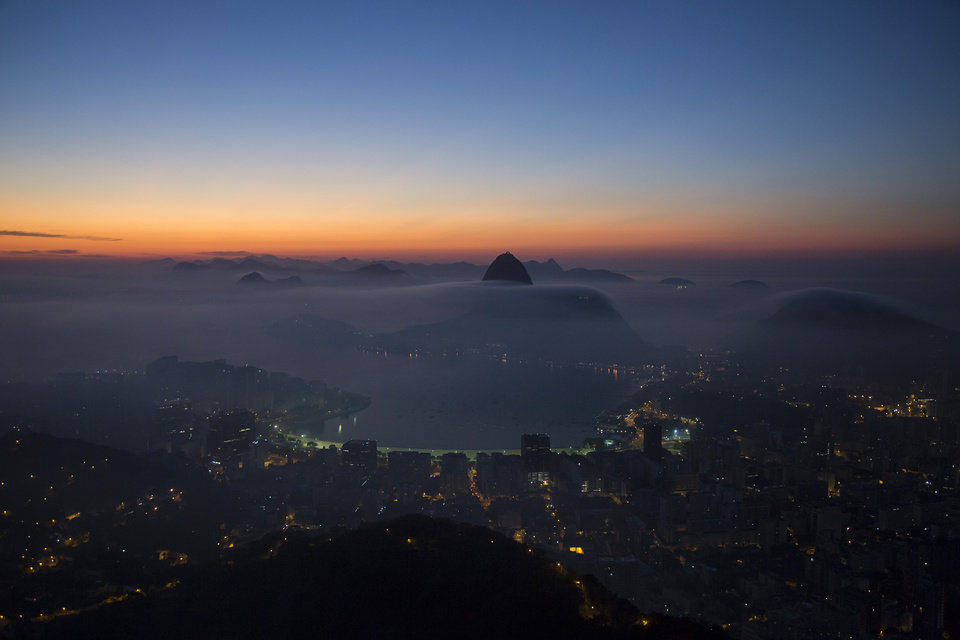 Photo - Sugarloaf Mountain and the Guanabara Bay are seen in a blanket of early morning fog as the sun begins to rise in Rio de Janeiro, Brazil, Friday, May 16, 2014. As opening day for the World Cup approaches, people continue to stage protests, some about the billions of dollars spent on the World Cup at a time of social hardship, but soccer is still a unifying force. The international soccer tournament will be the first in the South American nation since 1950. (AP Photo/Felipe Dana)