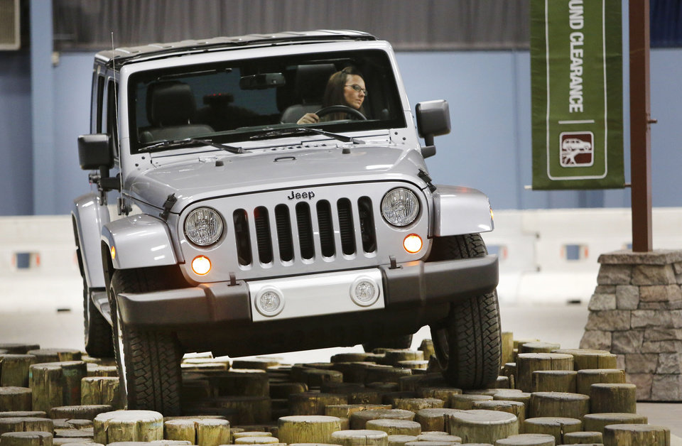 Photo - Visitors  can ride along wiht a professional driver in Camp Jeep, one of the interactive exhibits at the Oklahoma City International Auto Show. Here, Erin O'Connor drives a Jeep Wrangler through the obstacle course.  Steve Gooch - The Oklahoman