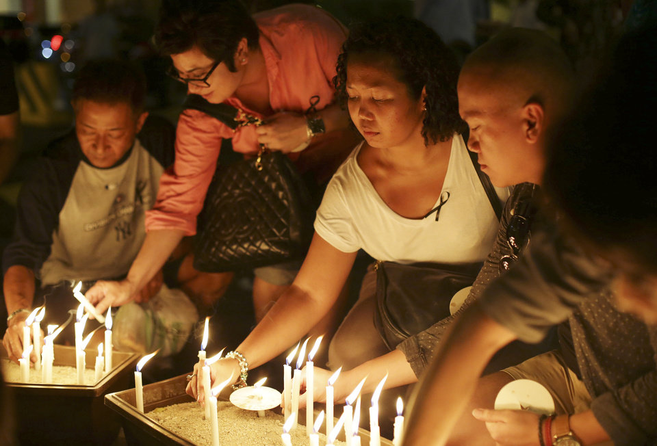 Photo - People place candles during a ceremony in memory of passengers on board the missing Malaysia Airlines Flight MH370 in Kuala Lumpur, Malaysia on Thursday, March 27, 2014. Australian officials say search operations for the missing Malaysia Airlines plane have been suspended for the day due to bad weather. (AP Photo/Aaron Favila)