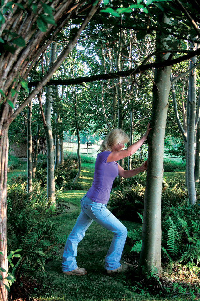 "This undated publicity photo released by courtesy Timber Press, shows Bunny Guinness using a tree to stretch for exercise from the book, ""Garden Your Way To Health and Fitness,"" by Bunny Guinness and Jacqueline Knox (Design, Bunny Guinness). Gardening can be a formidable workout and calorie burner, especially when adding calisthenics to the mix, along with stretching to avoid cramping and joint pain. (AP Photo/ Courtesy Timber Press)"