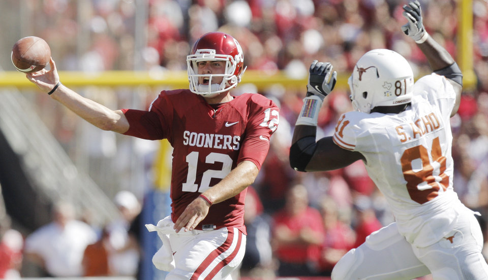 Photo - OU's Landry Jones (12) passes the ball on fourth down in the first quarter as Sam Acho (81) of Texas defends during the Red River Rivalry college football game between the University of Oklahoma Sooners (OU) and the University of Texas Longhorns (UT) at the Cotton Bowl on Saturday, Oct. 2, 2010, in Dallas, Texas. Photo by Nate Billings, The Oklahoman
