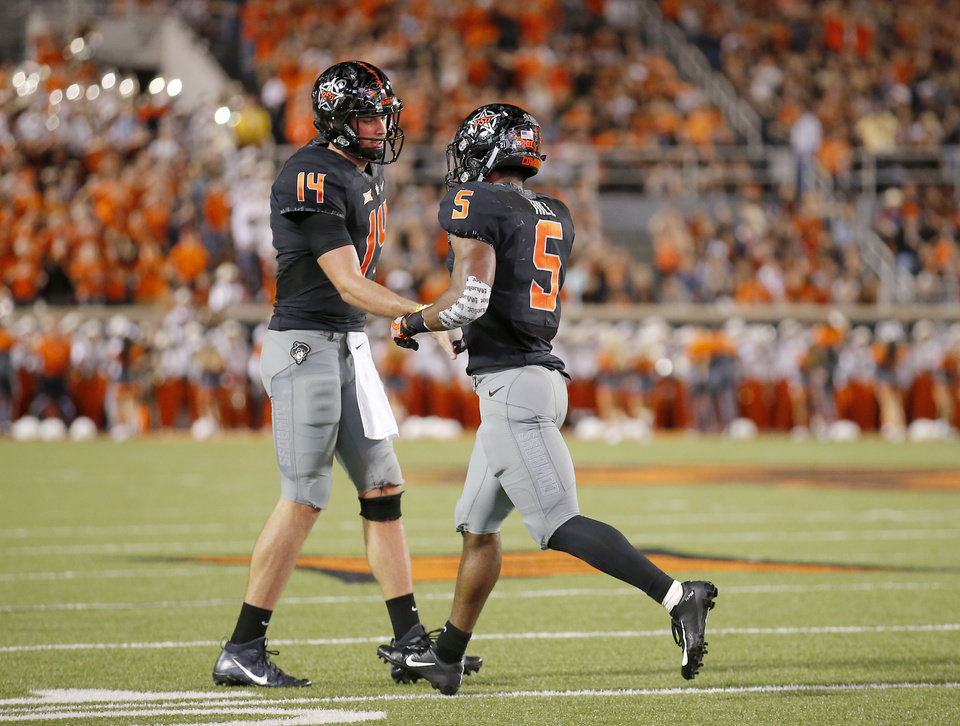 Photo - Oklahoma State's Taylor Cornelius (14) and Justice Hill (5) celebrate a touchdown in the second quarter during a college football game between Oklahoma State (OSU) and South Alabama at Boone Pickens Stadium in Stillwater, Okla., Saturday, Sept. 8, 2018. Photo by Sarah Phipps, The Oklahoman