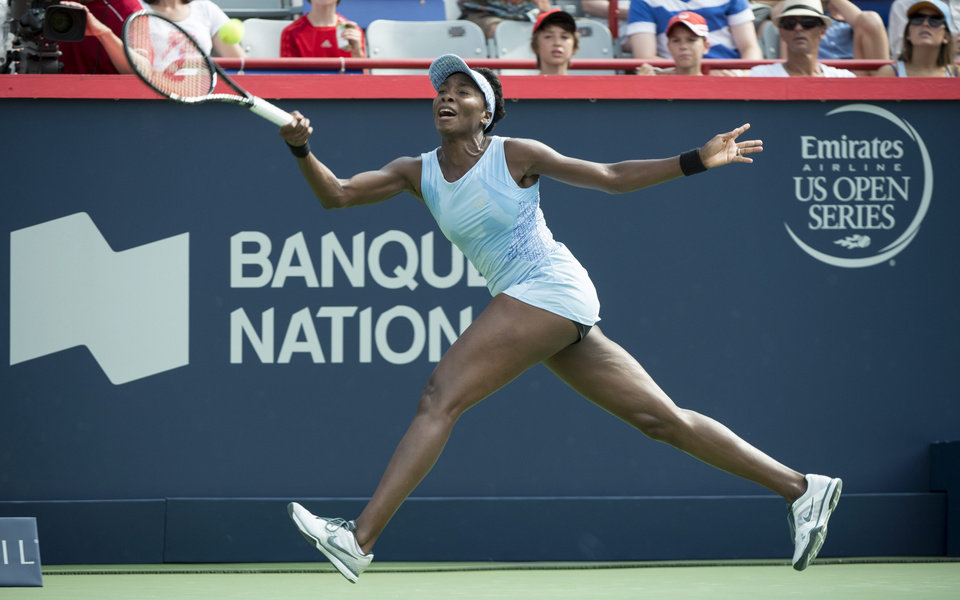 Photo - Venus Williams returns to Carla Suarez Navarro from Spain at the Rogers Cup tennis tournament, Friday, Aug. 8, 2014 in Montreal. (AP Photo/The Canadian Press, Paul Chiasson)
