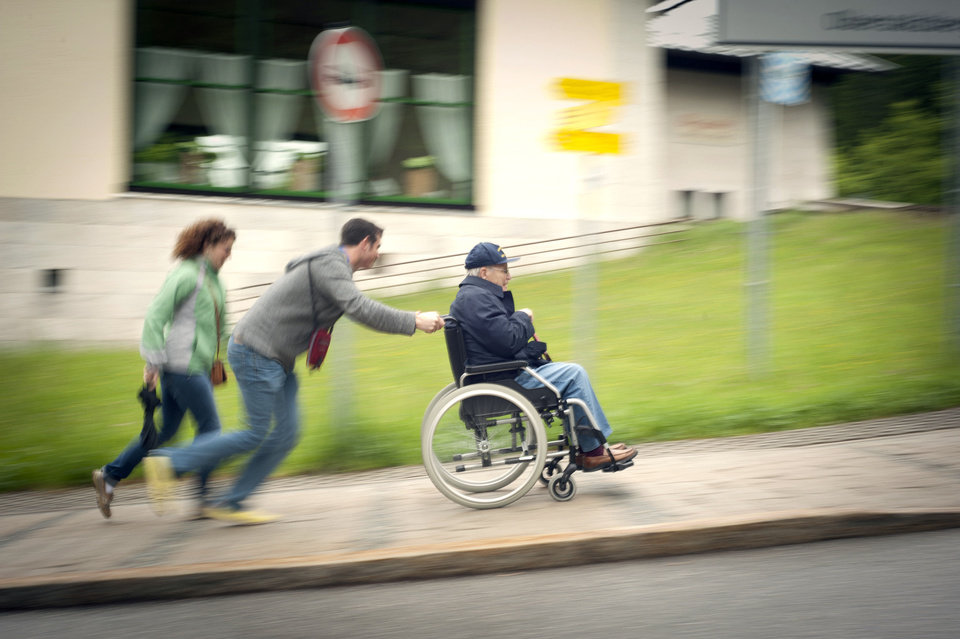Photo - College of the Ozarks students Ashley Bench and Austin Plummer race up a hill pushing Edmond resident Duncan Hall in a wheelchair in Berchtesgaden, Germany, during a recent tour of Concentration Camps. The tour was part of College of the Ozarks' Patriotic Education Travel Program