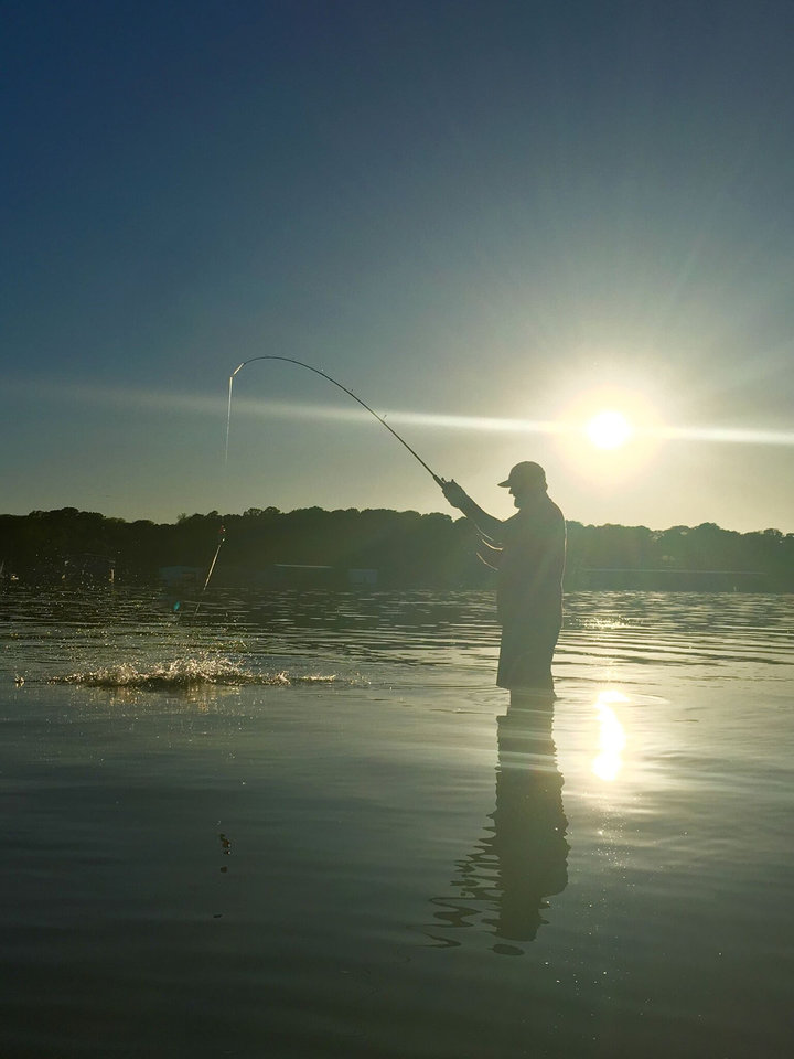Photo -  A fisherman reels in his catch on Lake Texoma. [PHOTO PROVIDED BY JASON HIGHTOWER/LAKE HOMES REALTY]