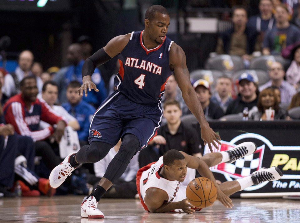 Photo - Atlanta Hawks forward DeMarre Carroll (4) steals the ball from Toronto Raptors guard Kyle Lowry, right, during the first half of an NBA basketball game in Toronto on Sunday, March 23, 2014. (AP Photo/The Canadian Press, Nathan Denette)