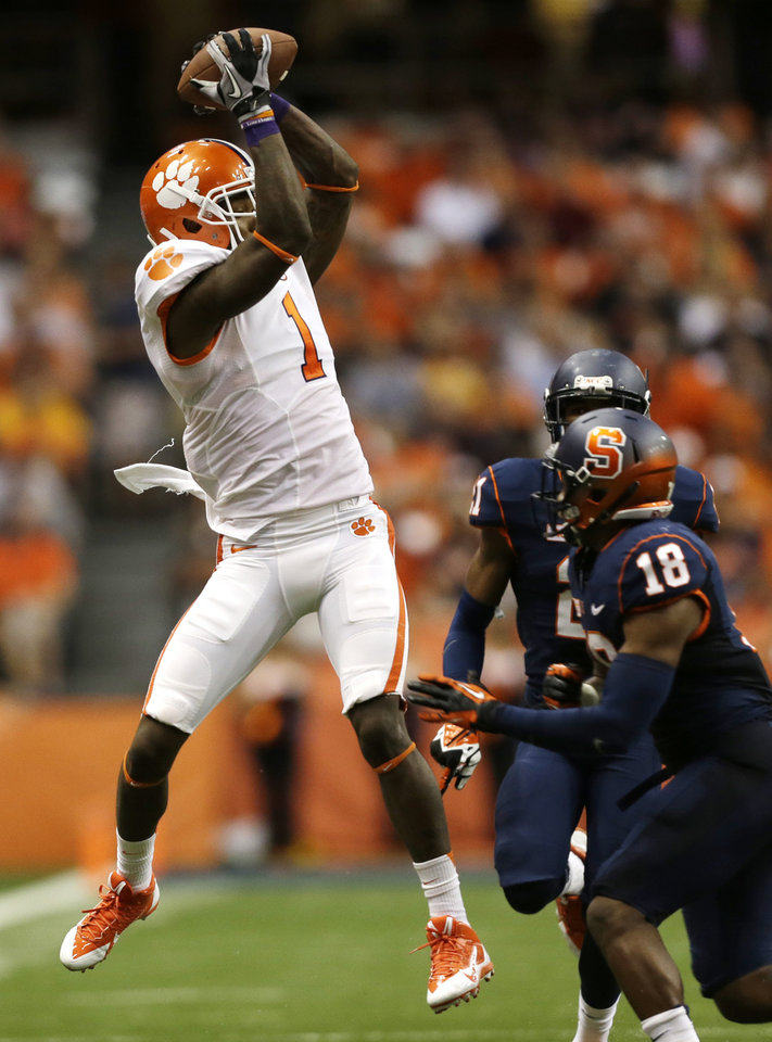 Photo - Clemson wide receiver Martavis Bryant (1) makes a catch in front of Syracuse defensive back Darius Kelly (18) during the first half of an NCAA college football game on Saturday, Oct. 5, 2013, in Syracuse, N.Y. (AP Photo/Mike Groll)