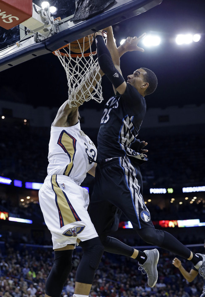Photo - Minnesota Timberwolves guard Kevin Martin, right, goes to the basket against New Orleans Pelicans power forward Anthony Davis, left, in the first half of an NBA basketball game in New Orleans, Friday, Feb. 7, 2014. (AP Photo/Gerald Herbert)