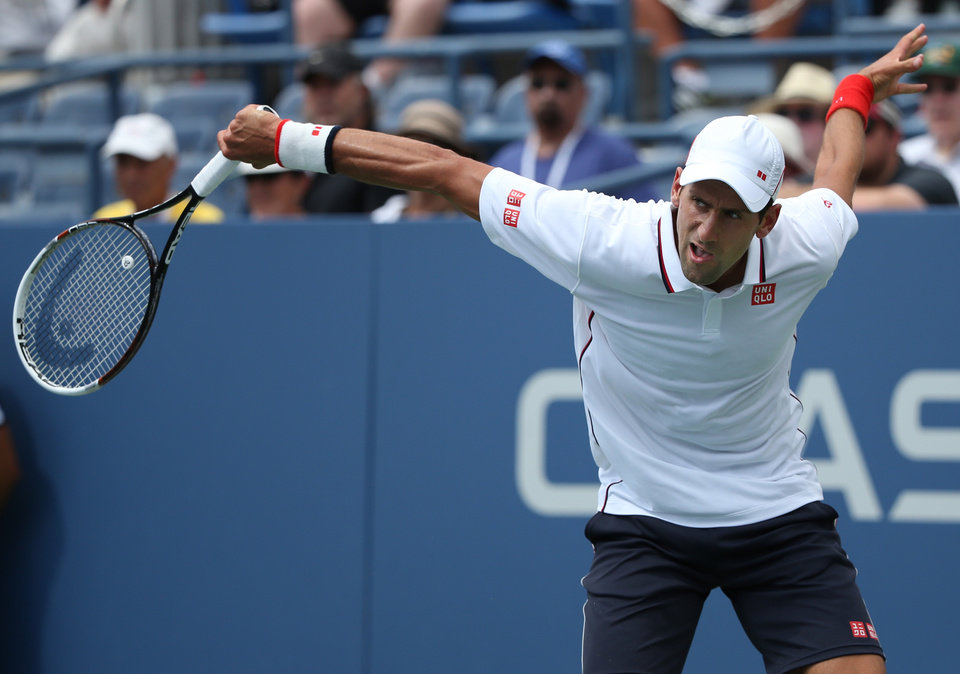 Photo - Novak Djokovic, of Serbia, follows through on a shot against Philipp Kohlschreiber, of Germany, during the fourth round of the 2014 U.S. Open tennis tournament, Friday, Aug. 29, 2014, in New York. (AP Photo/John Minchillo)