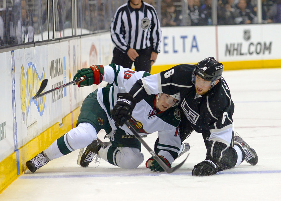 Photo - Minnesota Wild center Stephane Veilleux (19) and Los Angeles Kings defenseman Jake Muzzin (6) battle for the puck during the first period of an NHL hockey game, Monday, March 31, 2014, in Los Angeles. (AP Photo/Gus Ruelas)