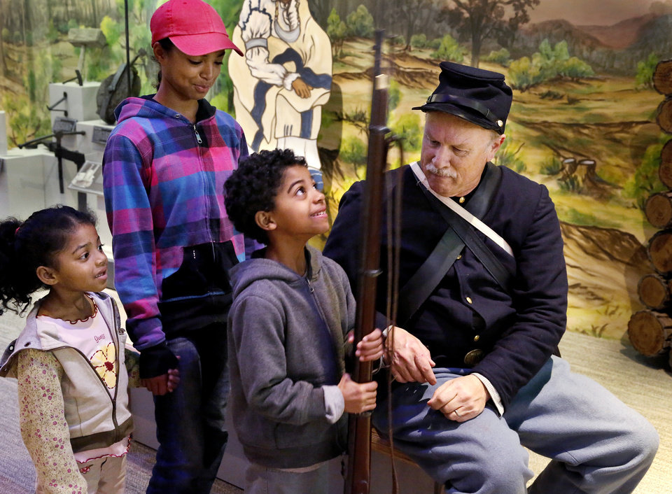 Three children talk to Walter Eskridge, a Civil War re-enactor and an assistant curator of education, at the Oklahoma History Center on Tuesday. Eskridge gave a talk to visiting campers about life as a soldier in the Civil War. After his presentation, some children approached Eskridge to ask more questions or hold his rifle and feel his uniform. The Oklahoma History Center hosted activities for children out of school for spring break at their Oklahoma History Camp. Photo by Jim Beckel, The Oklahoman Jim Beckel -