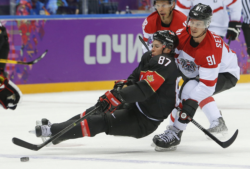 Photo - Canada forward Sidney Crosby loses his footing against Latvia forward Ronalds Kenins in the first period of a men's ice hockey game at the 2014 Winter Olympics, Friday, Feb. 14, 2014, in Sochi, Russia. (AP Photo/Mark Humphrey)