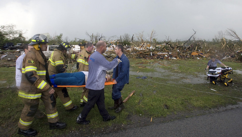 Photo - First responders carry an elderly woman away after they rescued her from the rubble of her home, after a tornado struck Wednesday, April 27, 2011 in Phil Campbell, Ala.  (AP Photo/TimesDaily, Daniel Giles)