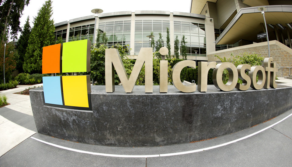 Photo - This photo taken with a fisheye lens on July 3, 2014 shows Microsoft Corp. signage outside the Microsoft Visitor Center in Redmond, Wash. Microsoft on Thursday, July 17, 2014 announced it will lay off 18,000 workers over the next year.  (AP Photo Ted S. Warren)