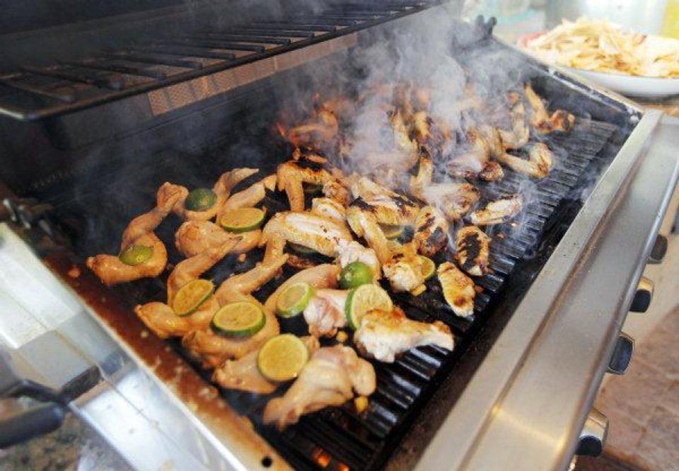 Photo - Chicken wings cook on a grill at American Propane, 7401 Broadway Extension. Photo by Nate Billings, The Oklahoman  NATE BILLINGS