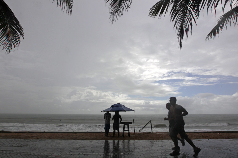 Photo - Joggers run in the rain at Ponta Negra beach in Natal, Brazil, Thursday, June 19, 2014. Japan play in group C of the 2014 soccer World Cup. (AP Photo/Shuji Kajiyama)