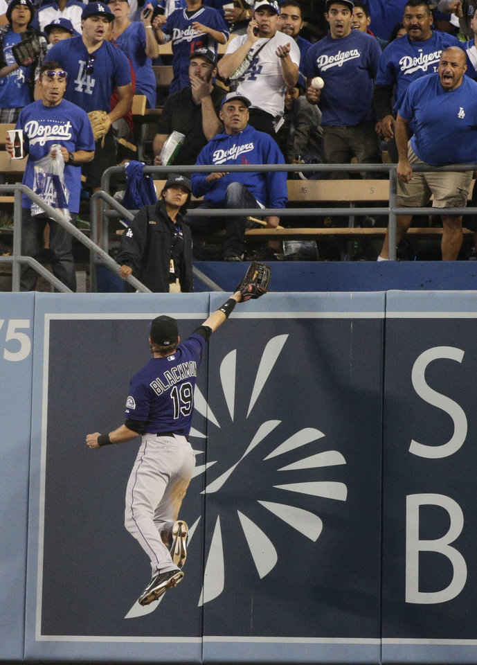Photo - Colorado Rockies right fielder Charlie Blackmon can't catch a two-run home run hit by Los Angeles Dodgers' Hanley Ramirez during the third inning of a baseball game on Tuesday, June 17, 2014, in Los Angeles. (AP Photo/Jae C. Hong)