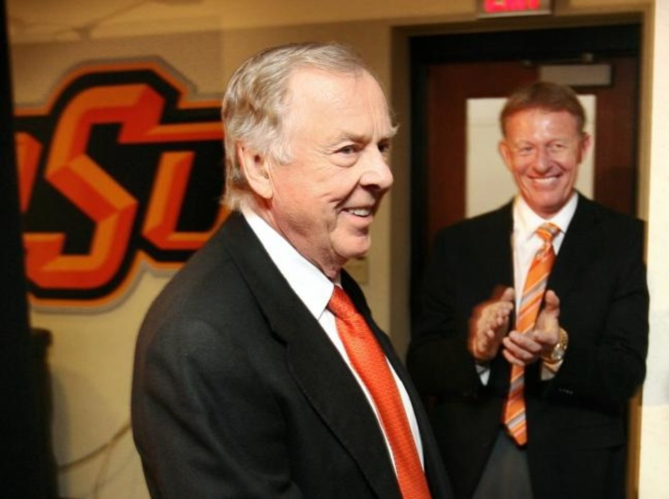 Photo -  Boone Pickens, left, receives applause from athletic director Mike Holder after the announcement of a $160 million gift to Oklahoma State's athletic department on Jan. 10, 2005. [Steve Sisney/Oklahoman archives]