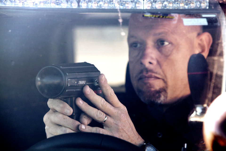 Photo - Kiowa Police Department Chief Tony Runyon and his handheld radar await the next speeder on U.S. 69 in Kiowa. Photo by David McDaniel, The Oklahoman  David McDaniel