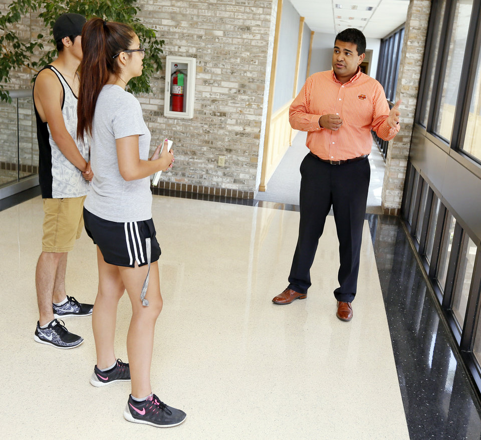 Photo -  Recruitment specialist Alfredo Melchor gives prospective students Brenda Galicia, 17, front, and Alejandro Escobar, 18, a campus tour at Oklahoma State University-Oklahoma City. [Photo by Nate Billings, The Oklahoman]