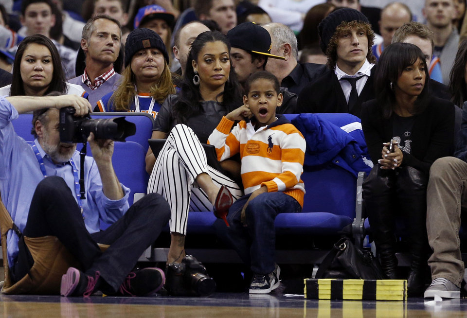 La La Vasquez, center, the wife of New York Knicks forward Carmelo Anthony, not pictured, sits with their young son Kiyan as they watch the NBA basketball game between Detroit Pistons and New York Knicks at the 02 arena in London, Thursday, Jan. 17, 2013.  (AP Photo/Matt Dunham)