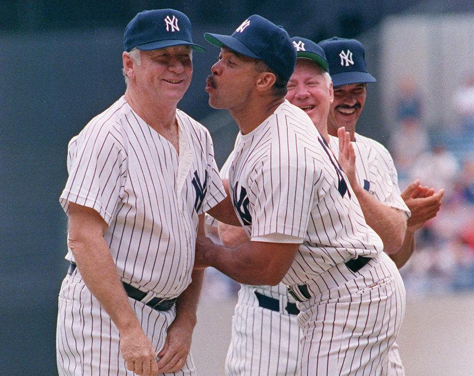 Photo - Former New York Yankees baseball player Mickey Mantle, left, gets a kiss from ex-Yankee Reggie Jackson during the Yankee's 45th Annual Old Timers Classic ceremony at Yankee Stadium in New York on Saturday, July 27, 1991.  Former Yankees ron Guidry, right, and Whitey Ford watch.  (AP Photo/Susan Ragan, File)