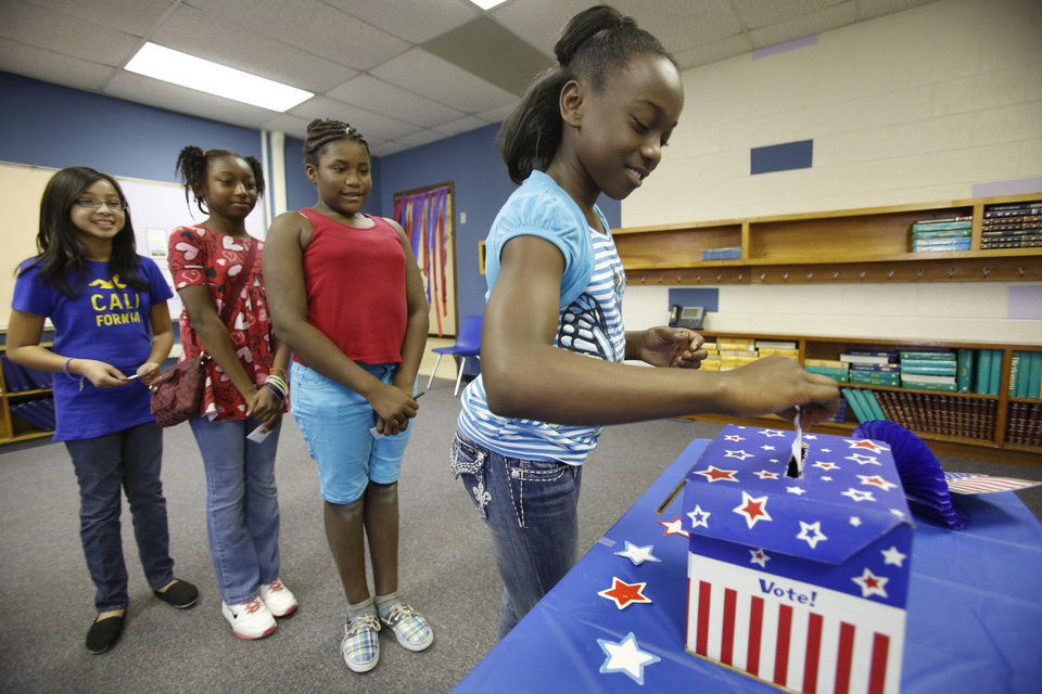 Fifth-grade students from left, Jennifer Nguyen, Semya Phanor, Napieria Murphy and Alexa Johnson, vote in a presidential election at Highland Park Elementary School in Del City on Friday. Photos by Steve Gooch, The Oklahoman