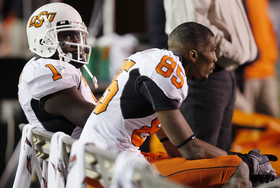 Photo - Oklahoma State's Dez Bryant (1) and Damian Davis (85) look on from the bench in the 56-20 loss to Texas Tech during the second half of the college football game between the Oklahoma State University Cowboys (OSU) and the Texas Tech Red Raiders at Jones AT&T Stadium on Saturday, Nov. 8, 2008, in Lubbock, Tex.BY CHRIS LANDSBERGER/THE OKLAHOMAN