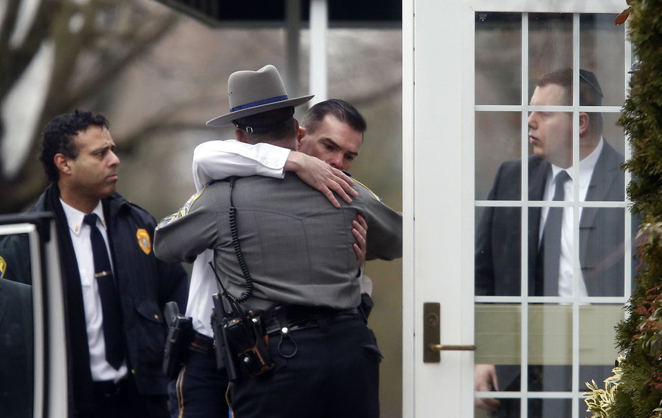 Photo - Police officers comfort one another outside a funeral service for 6-year-old Noah Pozner, Monday, Dec. 17, 2012, in Fairfield, Conn. Pozner was killed when a gunman walked into Sandy Hook Elementary School in Newtown Friday and opened fire, killing 26 people, including 20 children. (AP Photo/Jason DeCrow)