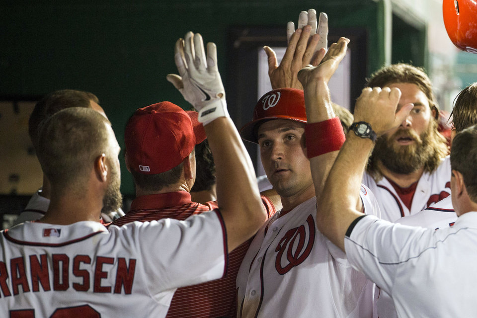 Photo - Washington Nationals Ryan Zimmerman is congratulated by teammates after scoring on a three-run double by Ian Desmond during the sixth inning of a baseball game against the Colorado Rockies at Nationals Park, on Monday, June 30, 2014, in Washington. (AP Photo/ Evan Vucci)