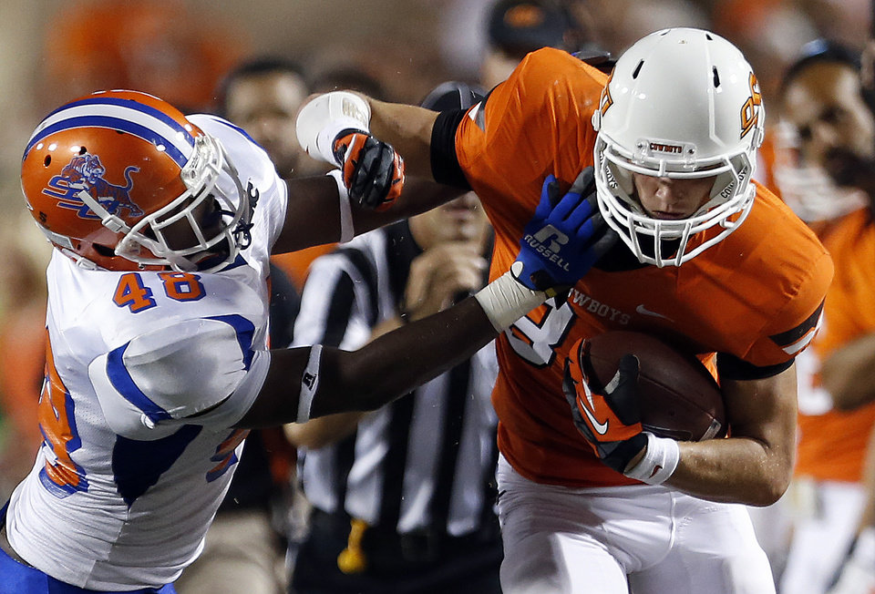 Oklahoma State's Austin Hays (84) fights off Savannah State's Edward Baety (48) during a college football game between Oklahoma State University (OSU) and Savannah State University at Boone Pickens Stadium in Stillwater, Okla., Saturday, Sept. 1, 2012. Photo by Sarah Phipps, The Oklahoman
