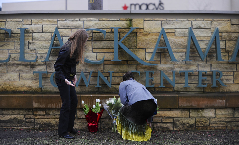Leslie King, right and Tenille Beseda place flowers Wednesday Dec. 12, 2012, at the entrance to the scene of a multiple shooting yesterday at Clackamas Town Center Mall in Portland, Ore.  A gunman who opened fire on shoppers at the mall had no connection to the two people he fatally shot and wanted to kill as many people as possible, police said Wednesday. (AP Photo/Greg Wahl-Stephens)  ORG XMIT: ORGW103