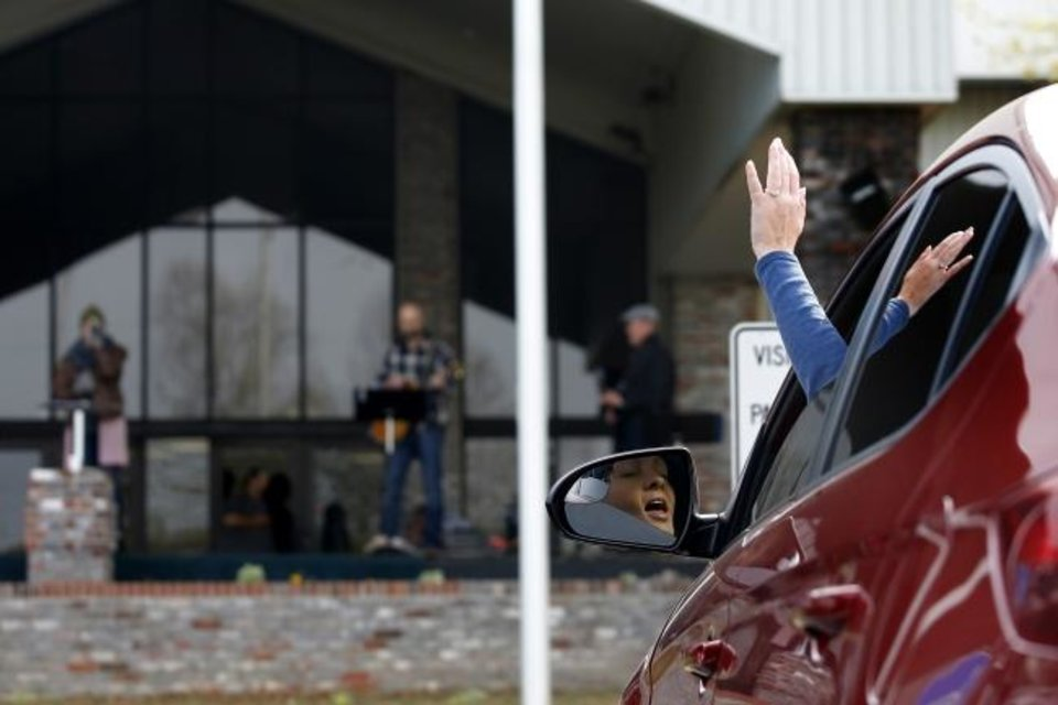 Photo -  Alicia Keating holds her hand up high as she sings while sitting in her car during