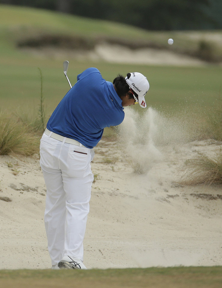 Photo - Hideki Matsuyama, of Japan, hits out of the bunker on the 14th hole during the first round of the U.S. Open golf tournament in Pinehurst, N.C., Thursday, June 12, 2014. (AP Photo/Charlie Riedel)