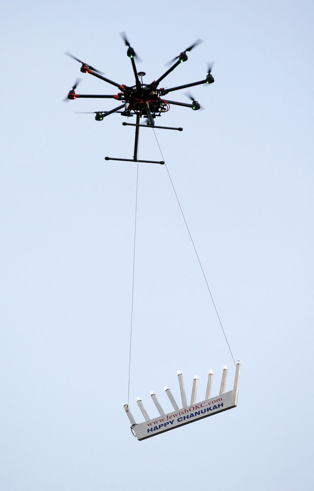 Photo -  A drone carries a flying menorah during a 2016 ceremony in downtown Oklahoma City. Officials with the Mike Monroney Aeronautical Center in Oklahoma City said more than 1 million drones have been registered with the Federal Aviation Administration in the past two years. [Photo by Nate Billings, The Oklahoman Archives]