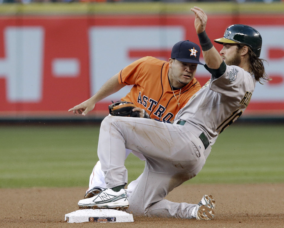 Oakland Athletics' Josh Reddick, right, steals second base despite the effort of Houston Astros' Jose Altuve during the first inning of a baseball game Friday, April 5, 2013, in Houston. (AP Photo/Pat Sullivan)