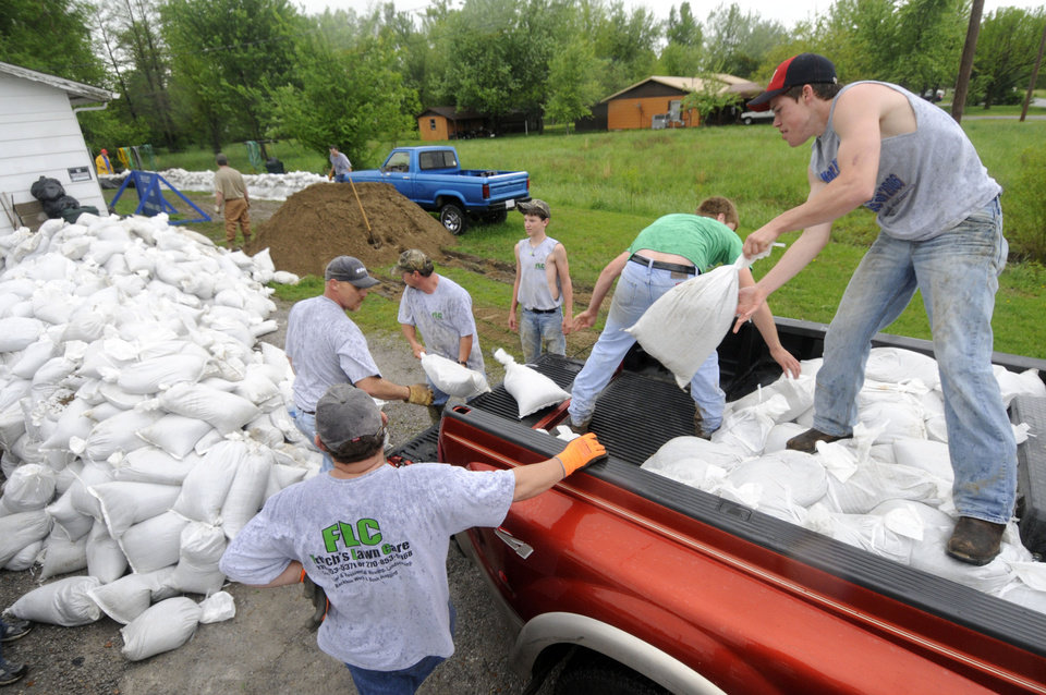 Photo - Volunteers empty sandbags from the back of a pick-up truck  in Metropolis, Ill.  Wednesday, April 27, 2011.  With five days of heavy rainfall and more to come, volunteers filling sandbags Wednesday in southern Illinois towns threatened by the swollen Ohio River braced for possible record flooding. Officials asked for more volunteers to help with the effort. (AP Photo/The Southern, Steve Jahnke)