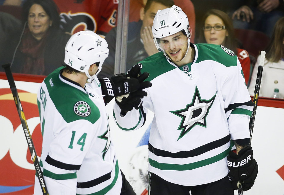 Photo - Dallas Stars' Tyler Seguin, right, celebrates his goal with teammate Jamie Benn during second-period NHL hockey game action against the Calgary Flames in Calgary, Alberta, Thursday, Nov. 14, 2013. (AP Photo/The Canadian Press, Jeff McIntosh)