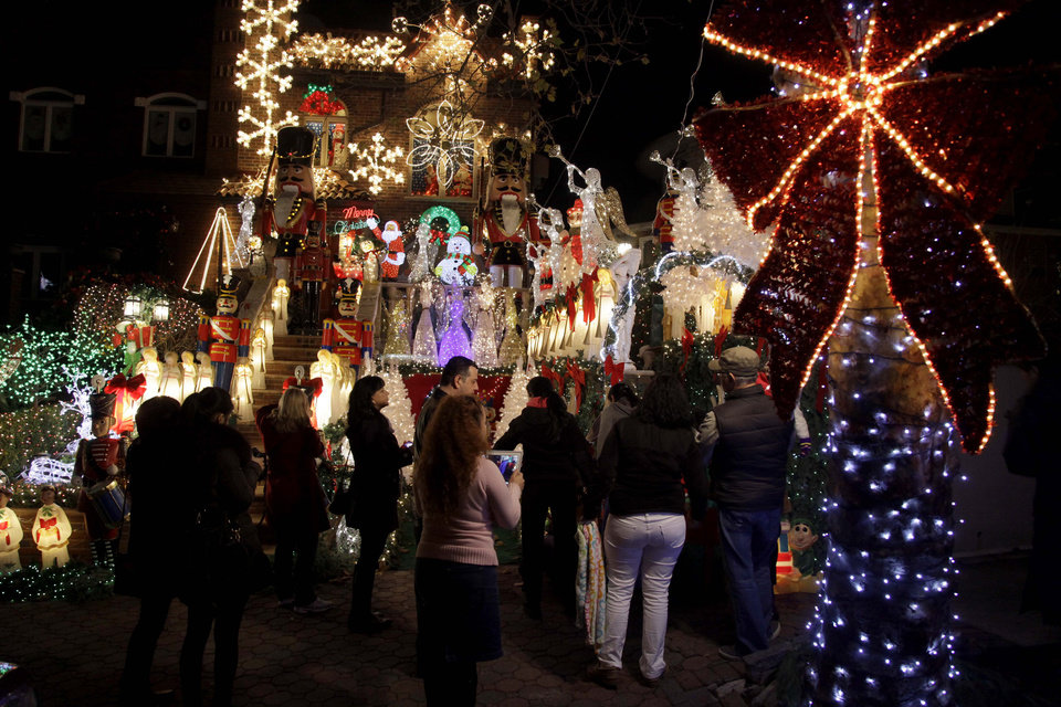 "This Dec. 4, 2012 photo shows spectators viewing an elaborately decorated home belonging to Lucy Spata in the Brooklyn borough of New York. Each holiday season, tour operator Tony Muia takes tourists from around the world on his ""Christmas Lights & Cannoli Tour"" visiting the Brooklyn neighborhoods of Dyker Heights and Bay Ridge, where locals take pride in over-the-top holiday light displays.  (AP Photo/Seth Wenig)"