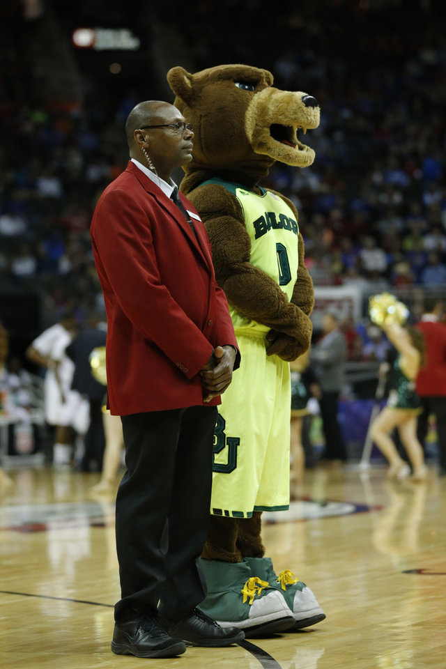 Photo - In this photo taken on March 14, 2014, the Baylor mascot stands with Sprint Center floor security during the first half of an NCAA college basketball game against Texas in the semifinals of the Big 12 Conference men's tournament in Kansas City, Mo. Security firms charged with protecting college and professional sports venues are monitoring social media more than ever to prepare for everything from a garden-variety court storming to something much more dangerous. (AP Photo/Orlin Wagner)
