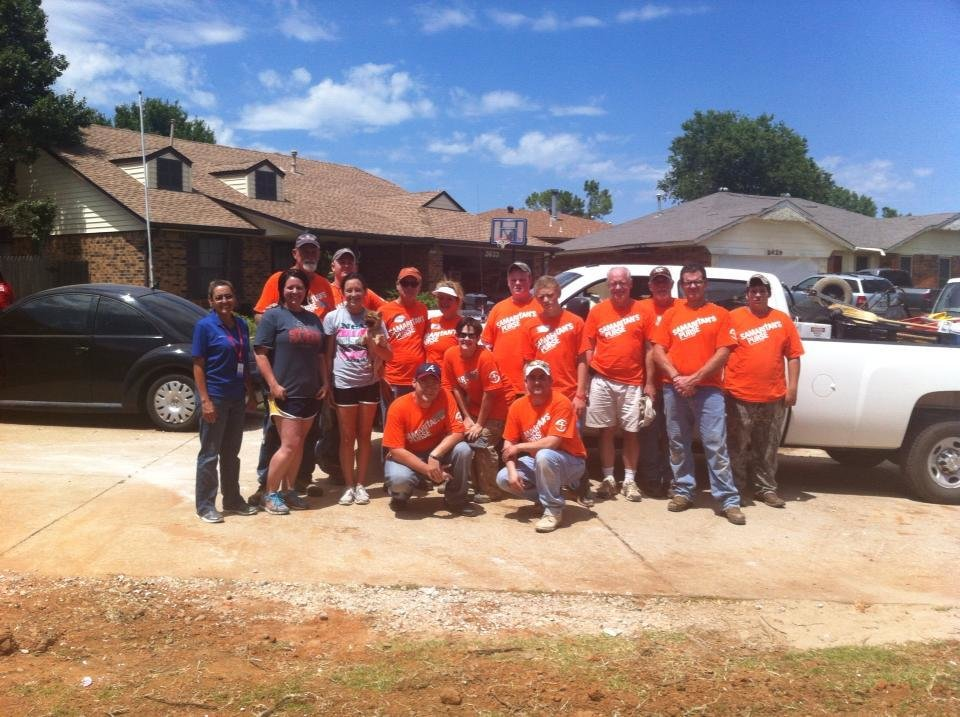 Photo -  Mike Armstrong poses for a picture with members of a team from Samaritan's Purse during disaster relief mission efforts in the aftermath of the May 2013 tornadoes in Oklahoma. Photo provided