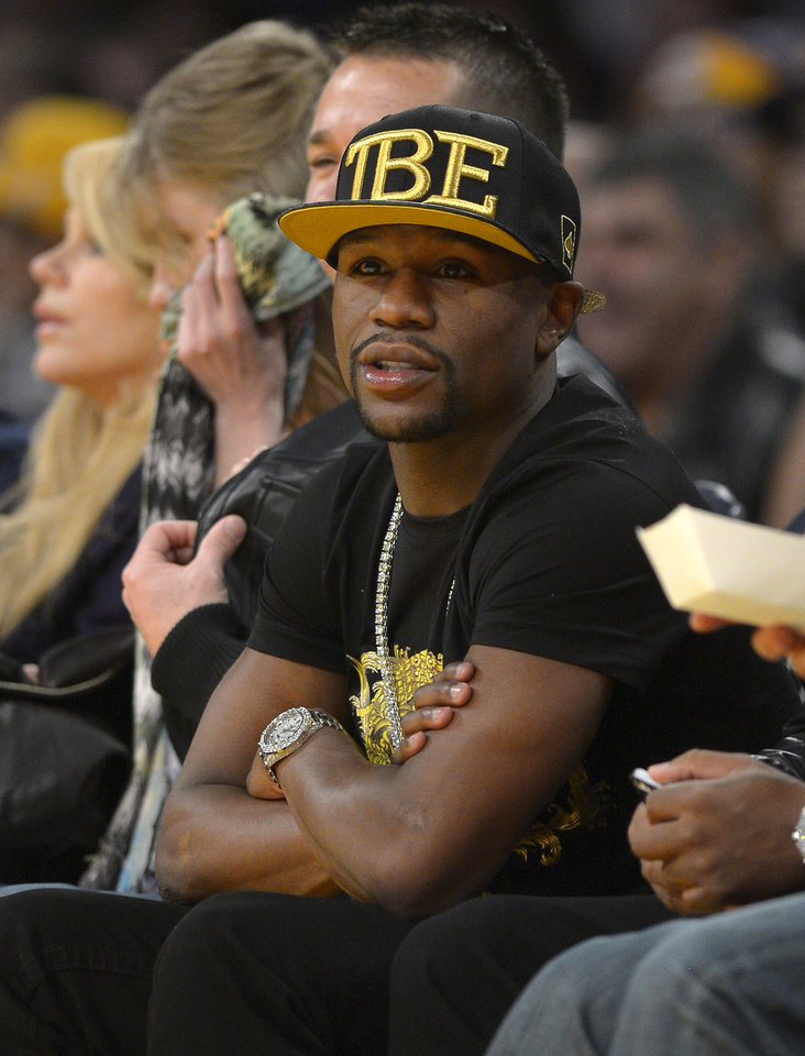 Photo - FILE - In this Nov. 24, 2013, file photo, Boxer Floyd Mayweather Jr. watches the Los Angeles Lakers play the Sacramento Kings during the first half of an NBA basketball game in Los Angeles. If Donald Sterling is compelled to sell the Los Angeles Clippers, the list of potential buyers will have more stars than the team's roster. Mayweather Jr. wants to form a group to buy the team.  (AP Photo/Mark J. Terrill, File)