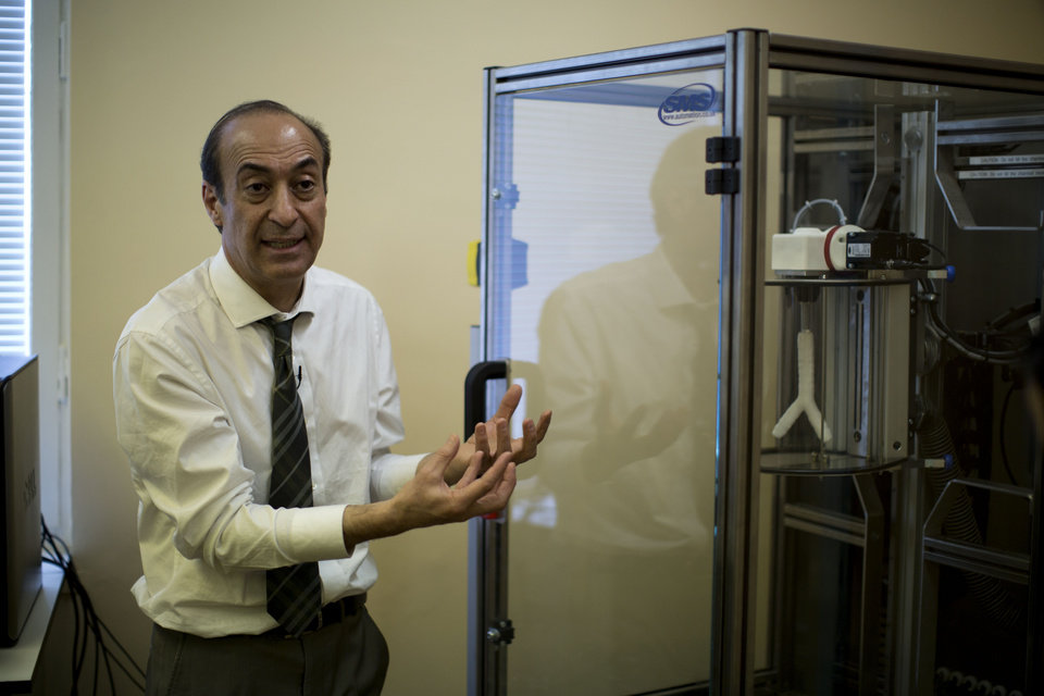 Photo - Professor Alexander Seifalian speaks next to an automated dip coating machine with a synthetic mould of a windpipe inside at his research facility in the Royal Free Hospital in London, Monday, March 31, 2014. In a north London hospital, scientists are growing noses, ears and blood vessels in the laboratory in a bold attempt to make body parts using stem cells. It is among several labs around the world, including in the U.S., that are working on the futuristic idea of growing custom-made organs in the lab. While only a handful of patients have received the British lab-made organs so far— including tear ducts, blood vessels and windpipes — researchers hope they will soon be able to transplant more types of body parts into patients, including what would be the world's first nose made partly from stem cells.