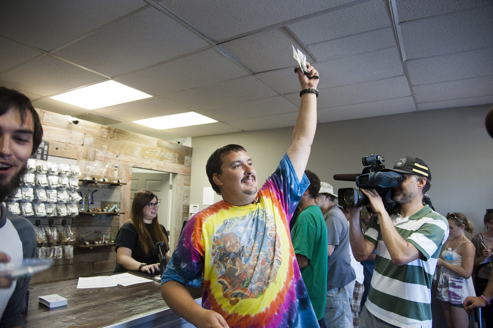 Mike Boyd turns to the crowd outside, showing off the 4 grams of marijuana he bought as the first in line to legally purchase marijuana at Spokane Green Leaf, Tuesday, July 8, 2014, in Spokane, Wash. Twenty months after voters legalized recreational cannabis for adults over 21, Washington state\'s first few licensed pot shops opened for business Tuesday, catering to hundreds of customers who lined up outside, thrilled to be part of the historic moment. (AP Photo/The Spokesman-Review, Dan Pelle)