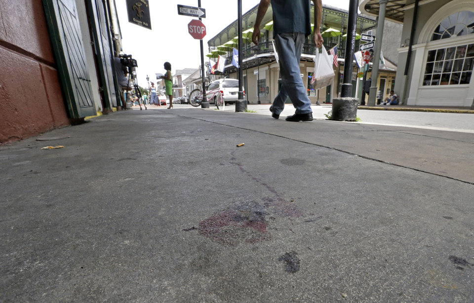 Photo - Blood stains are seen on the sidewalk at the scene of a shooting that happened early Sunday morning, June 29, 2014, on Bourbon Street in New Orleans. Nine people were injured, one seriously, according to New Orleans Police. (AP Photo/Gerald Herbert)