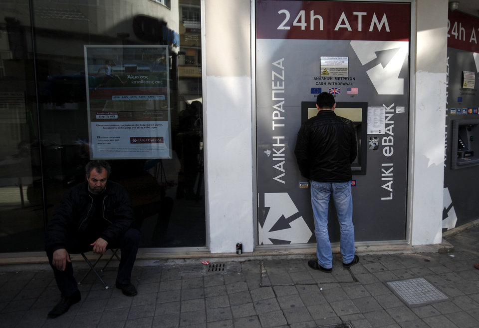 Photo - A man uses the ATM machine as another man sits outside of a closed branch of Laiki bank in capital Nicosia, Cyprus, Monday, March 25, 2013. Cyprus clinched a last-minute solution to avert imminent financial meltdown early Monday after it agreed to slash its oversized banking sector and inflict hefty losses on wealthy depositors in troubled banks to secure a 10 billion euro ($13 billion) bailout. (AP Photo/Petros Karadjias)