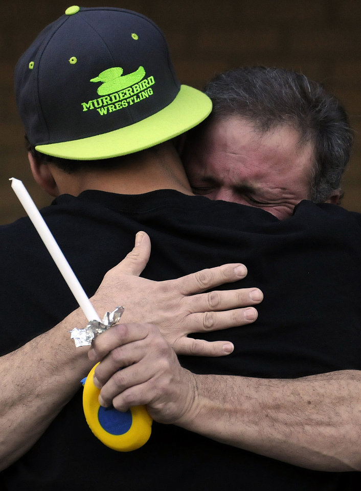 Photo -   Marcus Graham, left, hugs Reed Collar, father of former Wetupmka student and wrester Gilbert Collar, at a vigil on Tuesday, Oct. 9, 2012, at the high school in Wetumpka, Ala. Collar was shot and killed by a University of South Alabama police officer on Oct. 6. (AP Photo/Montgomery Advertiser, Amanda Sowards)