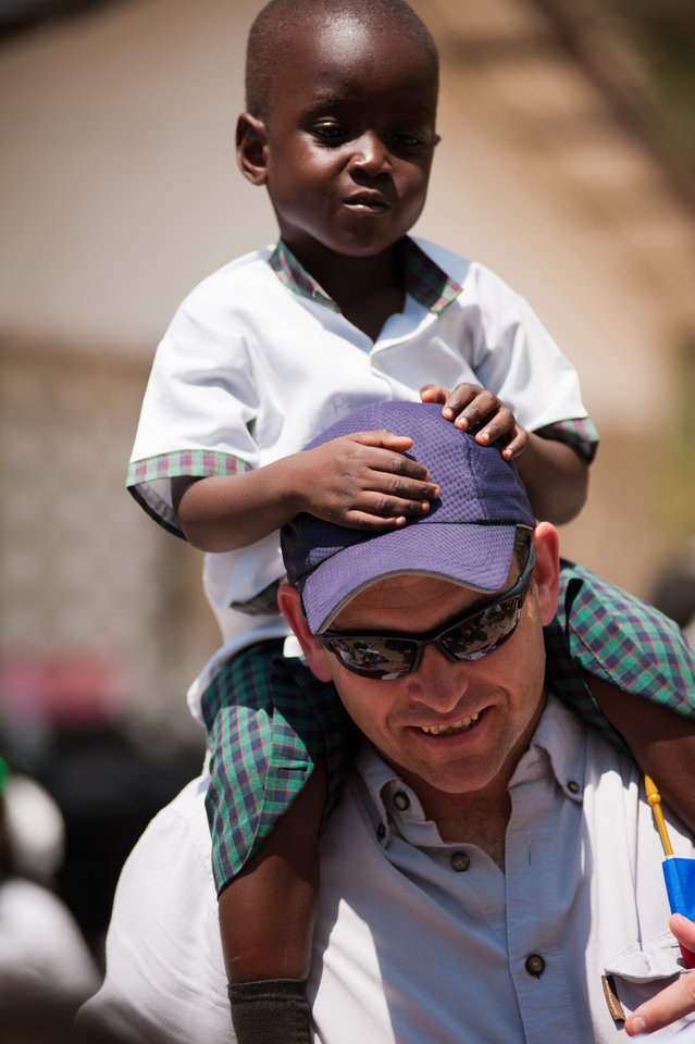 Photo - Darrell Kelly, SandRidge Energy's director of planning and optimization, totes a young boy on his shoulders in Frettas, Haiti. SandRidge volunteers have made three trips to Haiti since summer 2011.   - Provided