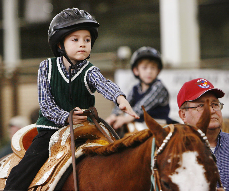 Photo - David, 7, (his last name cannot be used because he is a foster child) pets his horse in the arena inside Barn 1 at State Fair Park during a special segment called