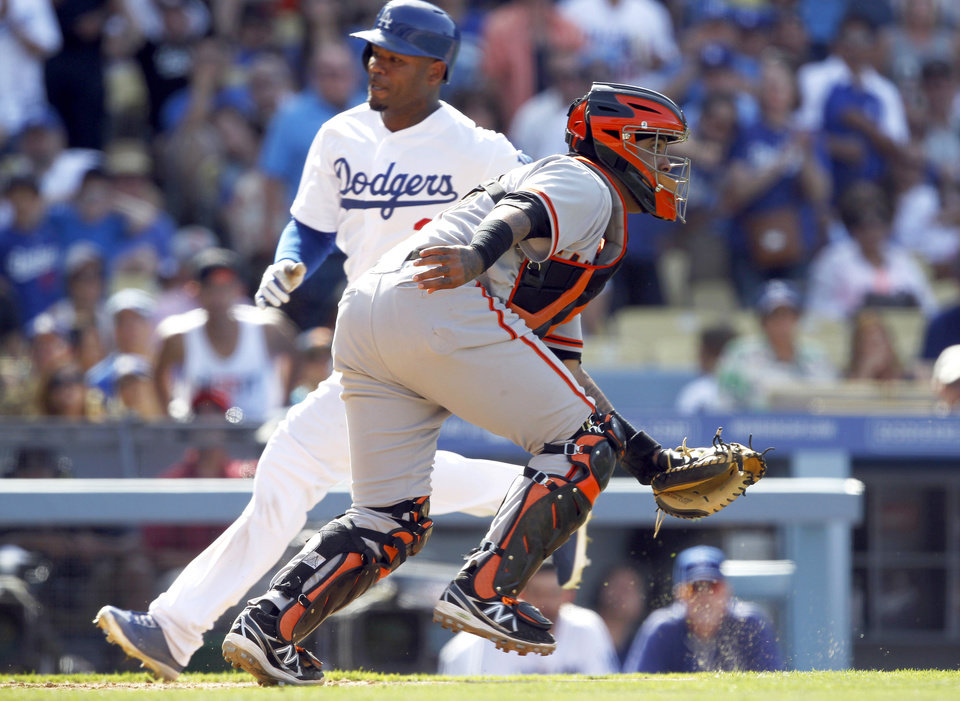 Photo - Los Angeles Dodgers' Carl Crawford, left, scores as the ball to San Francisco Giants catcher Hector Sanchez, right,  goes offline on a sacrifice fly to center by Dodgers' Drew Butera in the eighth inning of a baseball game on Saturday, May 10, 2014, in Los Angeles. The Dodgers won 6-2. (AP Photo/Alex Gallardo)